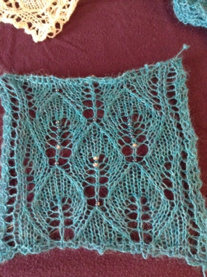 "A small blocked swatch of the turquoise shawl, with several ""test"" beads. I settled on the dark, metallic blue."